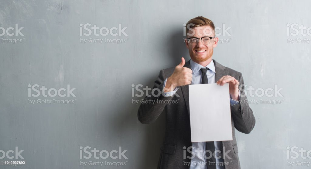 Young redhead  business man over grey grunge wall holding blank paper contract happy with big smile doing ok sign, thumb up with fingers, excellent sign stock photo