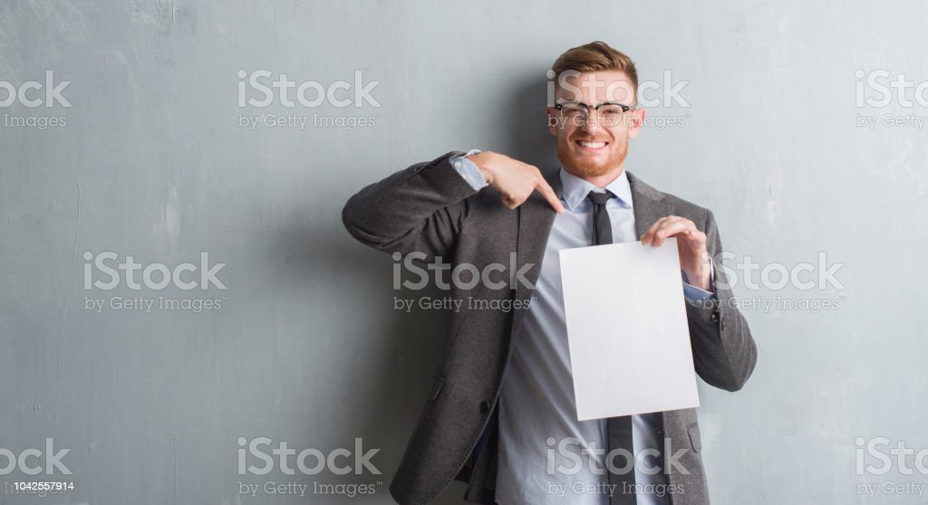 Young redhead  business man over grey grunge wall holding blank paper contract with surprise face pointing finger to himself stock photo
