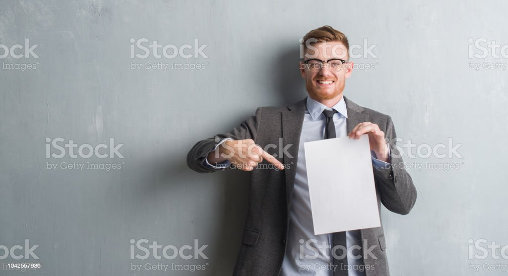 Young redhead  business man over grey grunge wall holding blank paper contract very happy pointing with hand and finger stock photo
