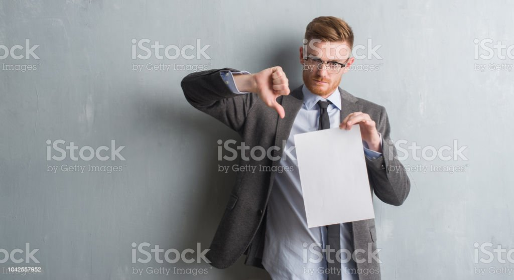 Young redhead  business man over grey grunge wall holding blank paper contract with angry face, negative sign showing dislike with thumbs down, rejection concept stock photo