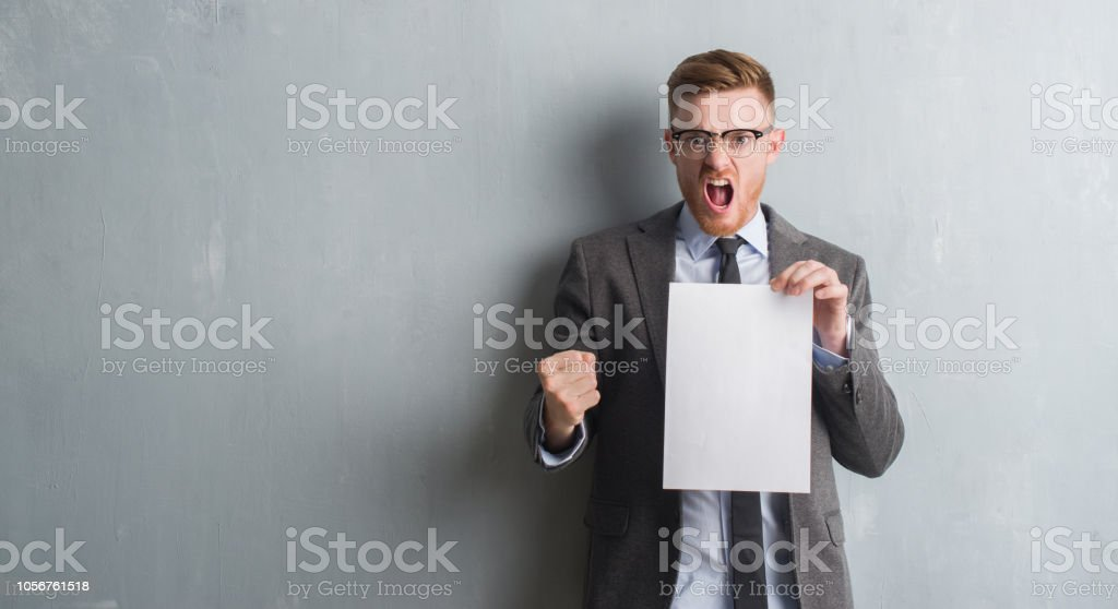 Young redhead  business man over grey grunge wall holding blank paper contract annoyed and frustrated shouting with anger, crazy and yelling with raised hand, anger concept stock photo