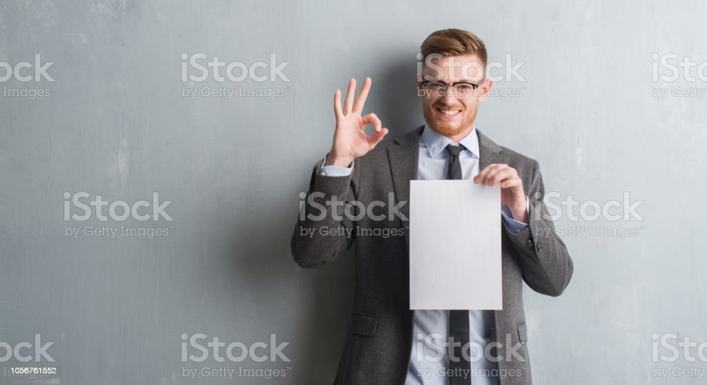 Young redhead  business man over grey grunge wall holding blank paper contract doing ok sign with fingers, excellent symbol stock photo