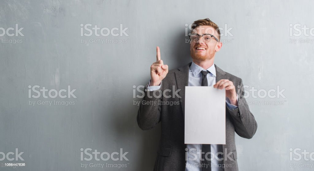Young redhead  business man over grey grunge wall holding blank paper contract surprised with an idea or question pointing finger with happy face, number one stock photo