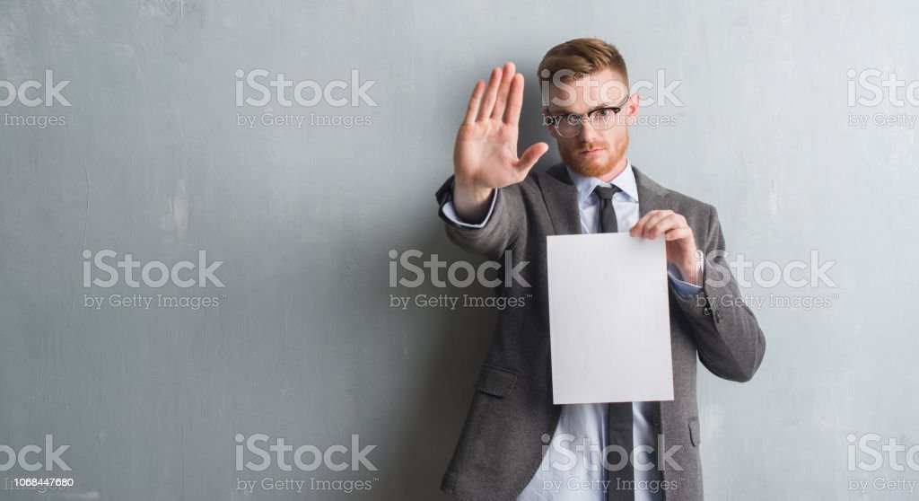 Young redhead  business man over grey grunge wall holding blank paper contract with open hand doing stop sign with serious and confident expression, defense gesture stock photo