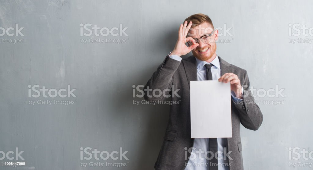 Young redhead  business man over grey grunge wall holding blank paper contract with happy face smiling doing ok sign with hand on eye looking through fingers stock photo