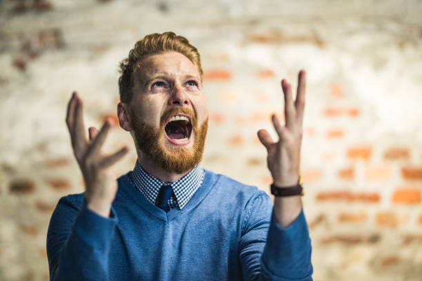 Young redhead businessman shouting from frustration. Frustrated businessman screaming of disappointment and looking up. agitation stock pictures, royalty-free photos & images