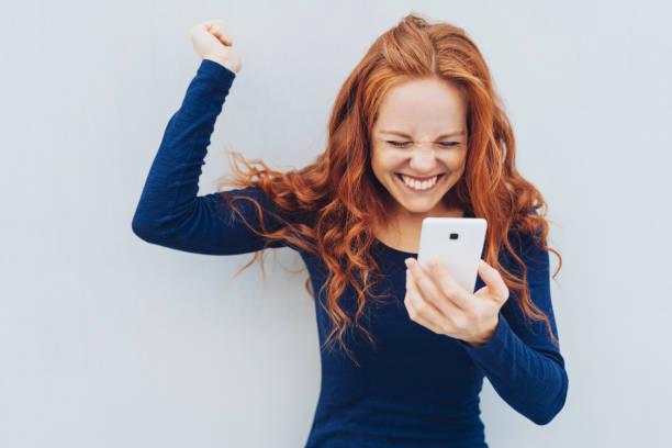 年輕的紅頭髮的人慶祝好消息 - 獲勝 個照片及圖片檔
