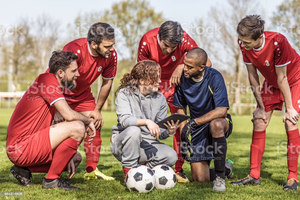 Young redhead Female Soccer Coach discussing tactics with her male...