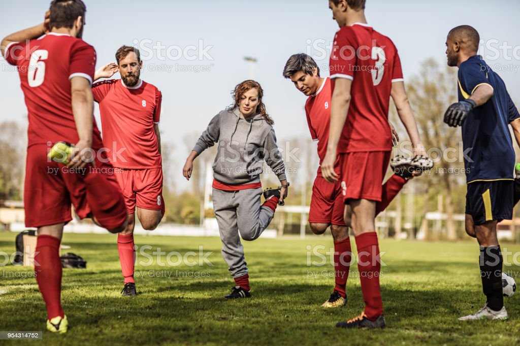 Young redhead Female Soccer Coach stretching with her male Football...