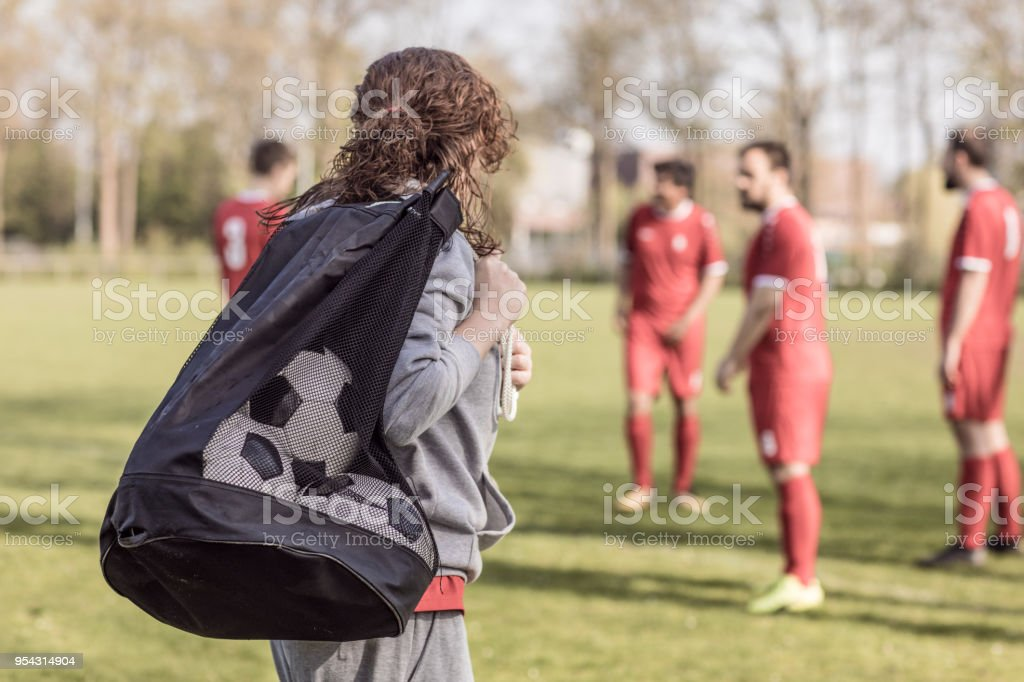 Young redhead Female Soccer Coach with her male Football team