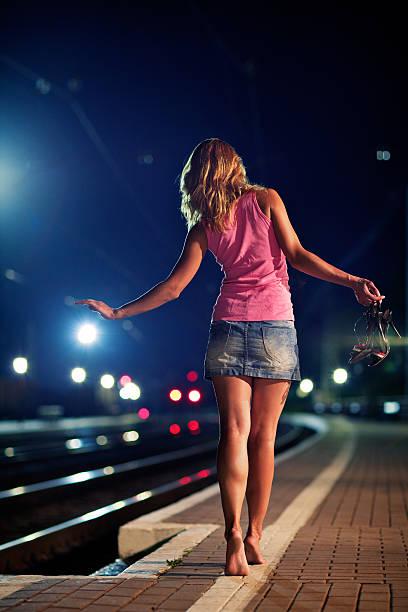 Young redhead girl goes tiptoe on the railway platform stock photo