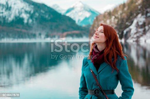 istock Young redhead girl in coat near lake in Alps 924647878