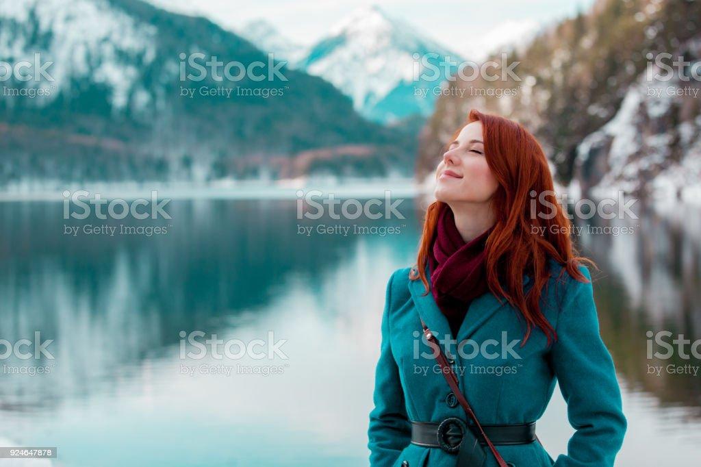Young redhead girl in coat near lake in Alps stock photo