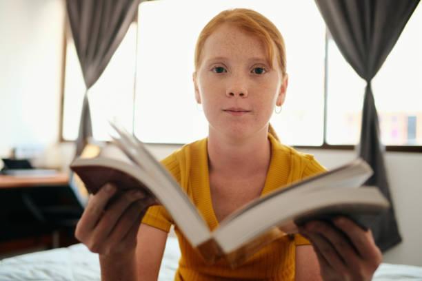 Junge Rothaarige Mädchen studieren und zeigen Buch vor der Kamera – Foto