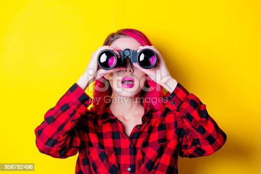 Young redhead girl with binoculars. Portrait isolated on yellow background