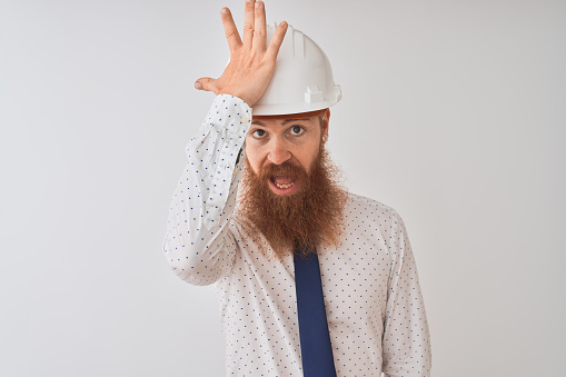 1046559700 istock photo Young redhead irish architect man wearing security helmet over isolated white background surprised with hand on head for mistake, remember error. Forgot, bad memory concept. 1204795061