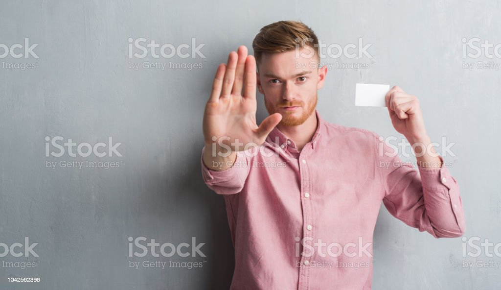 Young redhead man over grey grunge wall holding blank visit card with open hand doing stop sign with serious and confident expression, defense gesture stock photo