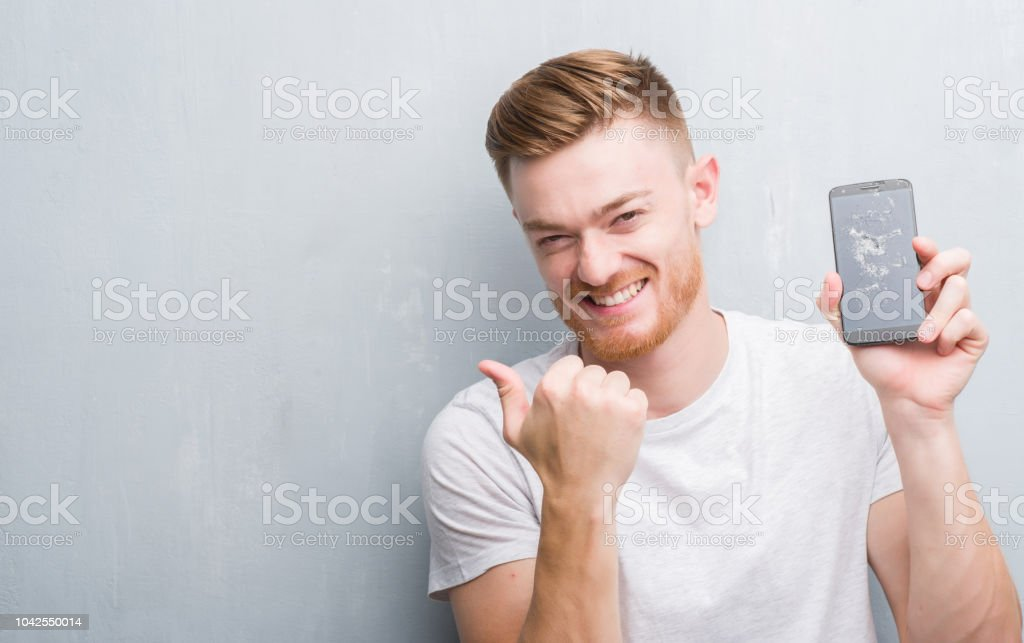 Young redhead man over grey grunge wall holding broken smartphone pointing and showing with thumb up to the side with happy face smiling stock photo