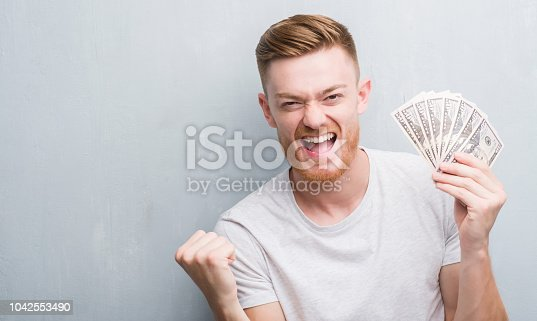 Young redhead man over grey grunge wall holding dollars screaming proud and celebrating victory and success very excited, cheering emotion