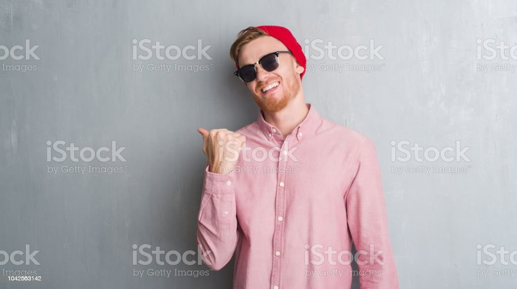 Young redhead man over grey grunge wall wearing wool cap and sunglasses  pointing and showing with thumb up to the side with happy face smiling -  Stock image . ee72de6f9ed