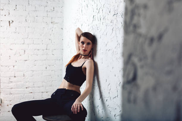 Young redhead model woman sitting on bar chair stock photo
