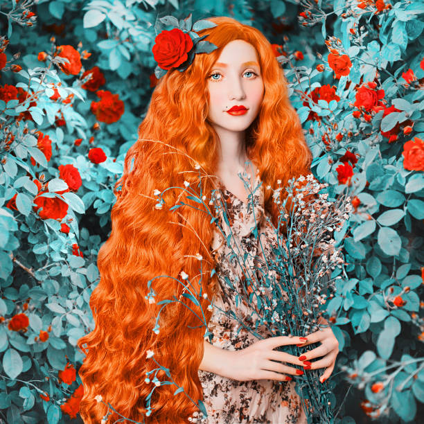 Young redhead renaissance woman in flower dress on rose background. A beautiful girl with pale skin, red lips and blue eyes. Renaissance princess in a spring garden with flowers in hands stock photo