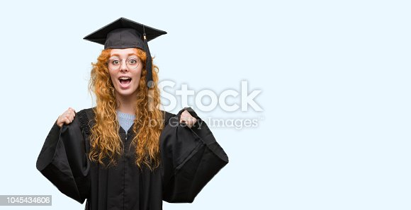 1175468850istockphoto Young redhead student woman wearing graduated uniform screaming proud and celebrating victory and success very excited, cheering emotion 1045434606