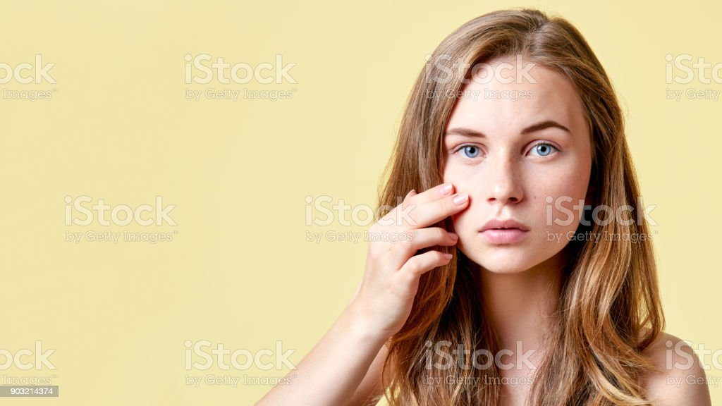 Young redhead teenager with self issues looking into mirror. Girl with low self esteem checking her skin in a mirror. stock photo