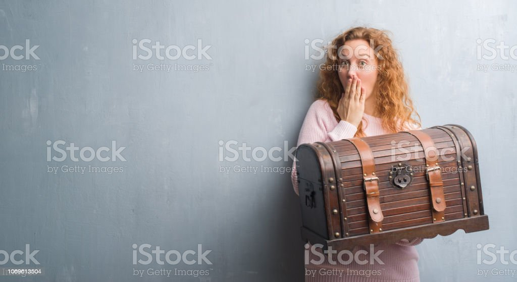 Young redhead woman holding vintage chest cover mouth with hand...