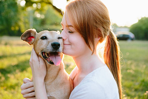 young redhead woman hug her small Mixed-breed dog stock photo