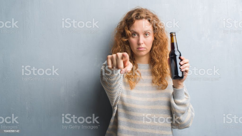Young redhead woman over grey grunge wall holding beer bottle pointing with finger to the camera and to you, hand sign, positive and confident gesture from the front Young redhead woman over grey grunge wall holding beer bottle pointing with finger to the camera and to you, hand sign, positive and confident gesture from the front Adult Stock Photo