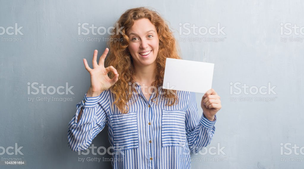 Young redhead woman over grey grunge wall holding blank card doing ok sign with fingers, excellent symbol stock photo