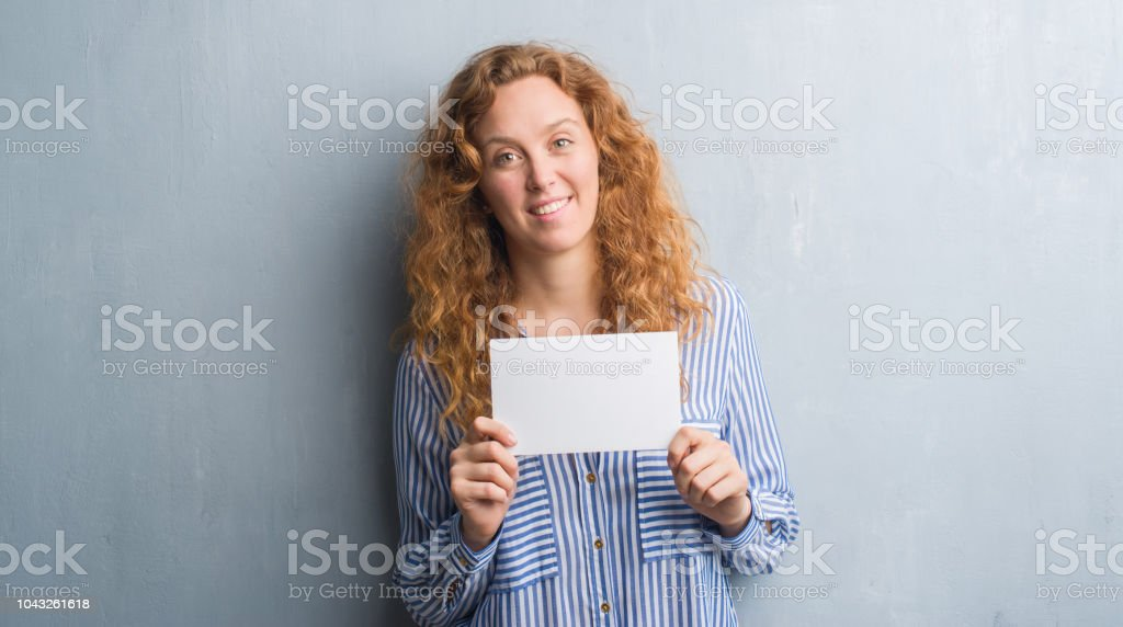 Young redhead woman over grey grunge wall holding blank card with a happy face standing and smiling with a confident smile showing teeth stock photo