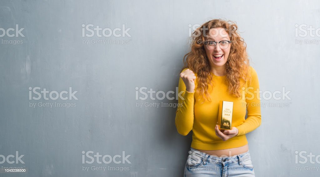 Young redhead woman over grey grunge wall holding gold ingot...