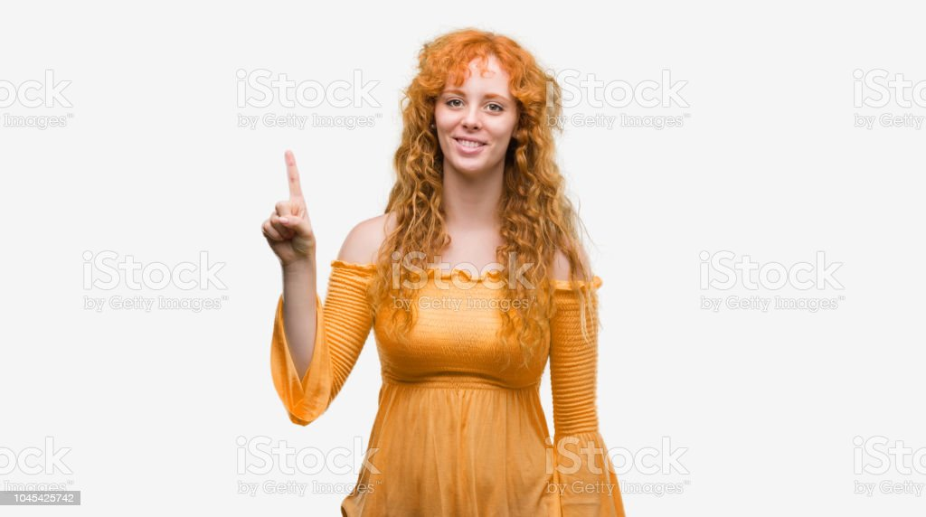 Young redhead woman showing and pointing up with finger number one while smiling confident and happy. stock photo