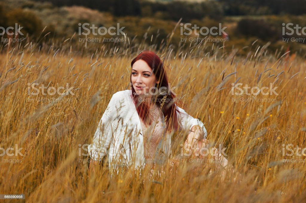 Young redhead woman sitting in the tall grass Lizenzfreies stock-foto