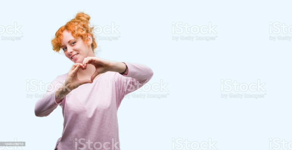 Young redhead woman smiling in love showing heart symbol and shape with hands. Romantic concept. stock photo