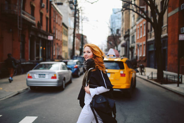 Young redhead woman walking on the streets of West Village, Manhattan, NY stock photo