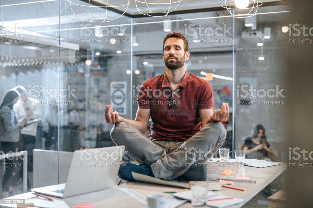 Ung avslappnad manliga företagare som utövar Yoga på bordet i kontoret. - Royaltyfri Affärsman Bildbanksbilder