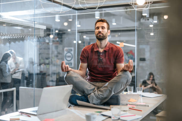 junge entspannt männliche unternehmer ausübung von yoga auf dem tisch im büro. - yoga fürs büro stock-fotos und bilder