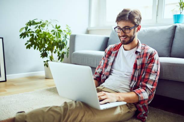 Junger entspannter Mann, der am Laptop arbeitet, während er zu Hause auf dem Boden sitzt – Foto