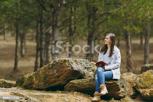 862602714istockphoto Young relaxing smiling beautiful woman in casual clothes sitting on stone studying reading book in big city park or forest on green background. Student learning, education. Lifestyle, leisure concept. 956317240