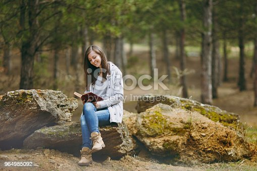 862602714istockphoto Young relaxing smiling beautiful woman in casual clothes sitting on stone studying reading book in big city park or forest on green background. Student learning, education. Lifestyle, leisure concept. 964985092