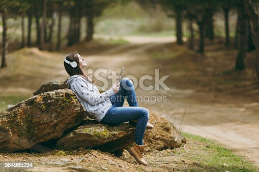 862602714istockphoto Young relaxing smiling beautiful woman in casual clothes with headphones sitting on stone using tablet pc computer in city park or forest on green background. Student lifestyle, leisure concept. 964985294
