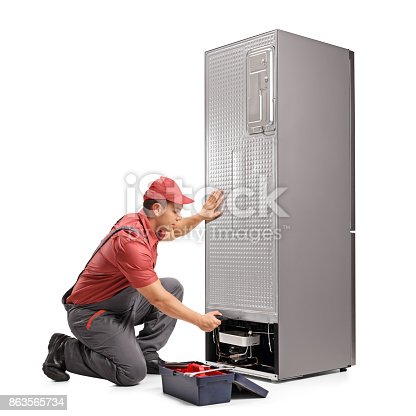 istock Young repairman fixing a refrigerator 863565734