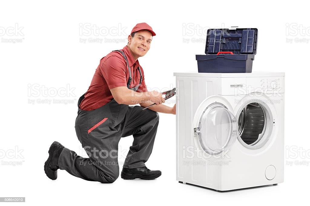 Young repairman fixing a washing machine stock photo