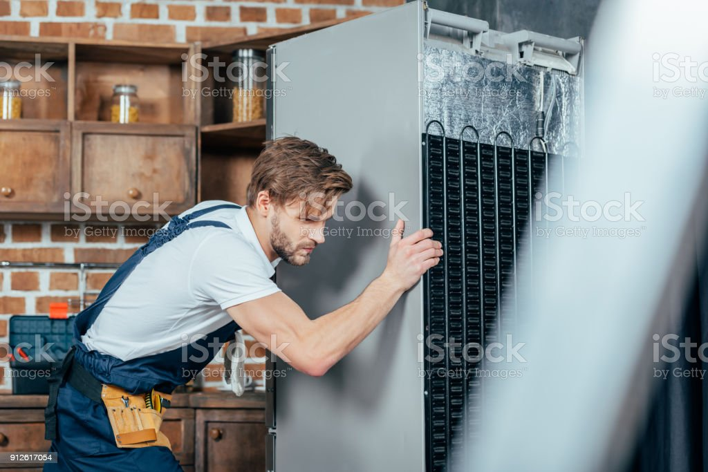 young repairman in protective workwear moving refrigerator in kitchen stock photo