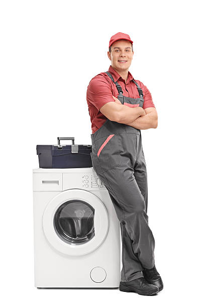 Young repairman leaning on a washing machine Full length portrait of a young male repairman leaning on a washing machine isolated on white background bib overalls stock pictures, royalty-free photos & images