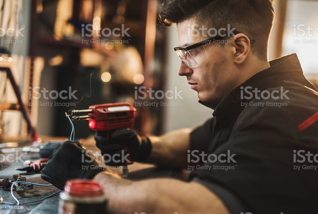 Young repairman working in workshop and soldering wires together. stock photo