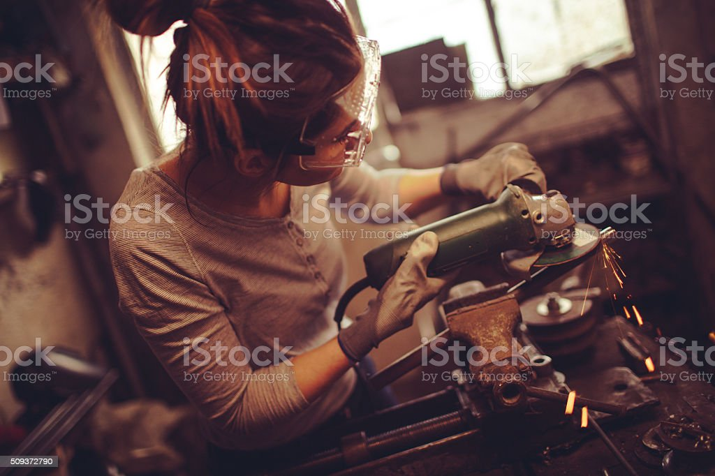 Young repairwoman using a grinder stock photo